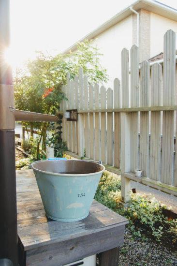 雨水を貯めたバケツと朝陽